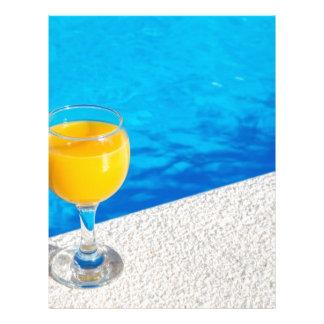Glass with orange juice on edge of swimming pool letterhead