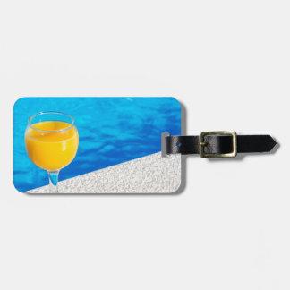Glass with orange juice on edge of swimming pool luggage tag