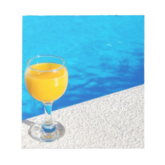 Glass with orange juice on edge of swimming pool notepads