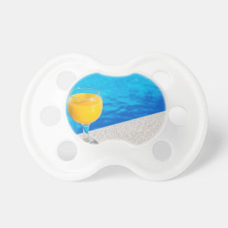 Glass with orange juice on edge of swimming pool pacifier
