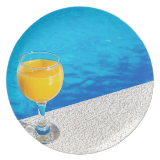 Glass with orange juice on edge of swimming pool party plate
