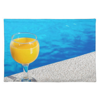 Glass with orange juice on edge of swimming pool placemat
