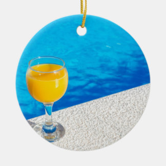 Glass with orange juice on edge of swimming pool round ceramic ornament