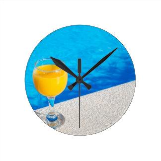 Glass with orange juice on edge of swimming pool round clock
