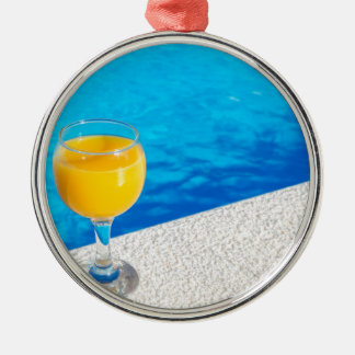 Glass with orange juice on edge of swimming pool Silver-Colored round ornament