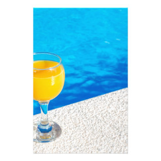 Glass with orange juice on edge of swimming pool stationery