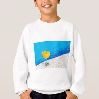 Glass with orange juice on edge of swimming pool sweatshirt