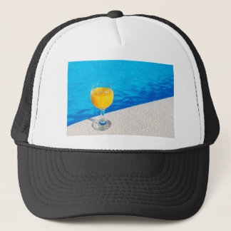 Glass with orange juice on edge of swimming pool trucker hat