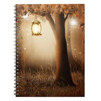 Glowing Lantern Hangs in tree during autumn dusk Notebook