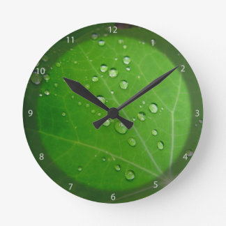 Glowing Raindrops on nasturtium leaf Round Clock