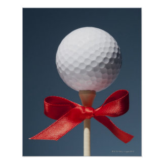 Gold ball on tee with red bow poster