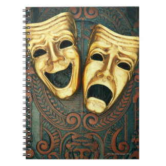 Golden comedy and tragedy masks on patterned notebook