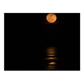 golden full moon over ocean postcard