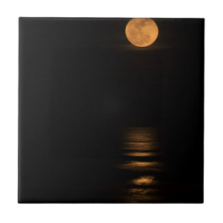 golden full moon over ocean tile