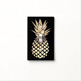 golden pineapple on black light switch cover
