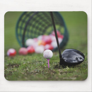 Golf ball on tee beside golf club mouse pad