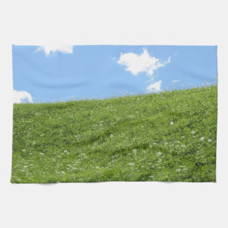 Grassy field at the rolling hill against the sky kitchen towels
