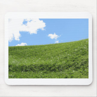 Grassy field at the rolling hill against the sky mouse pad