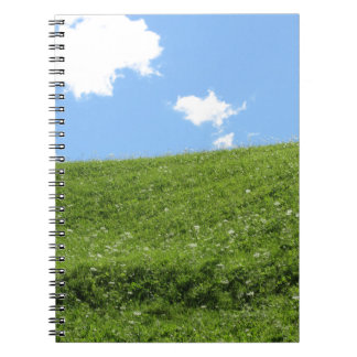 Grassy field at the rolling hill against the sky spiral notebook
