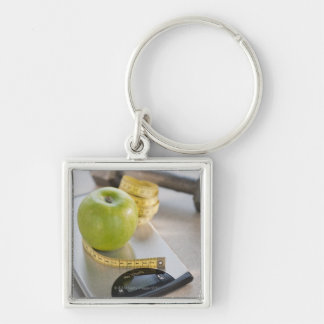 Green apple on weight scale, tape measure and key chains