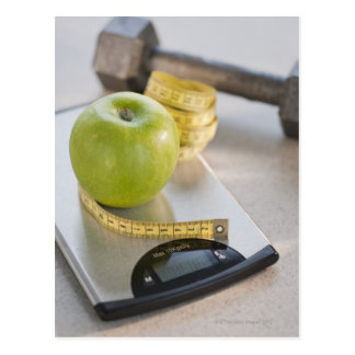 Green apple on weight scale, tape measure and post cards