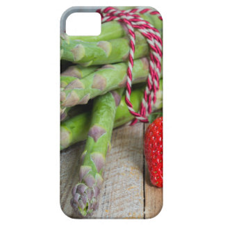 Green asparagus with strawberries on wooden iPhone 5 cover