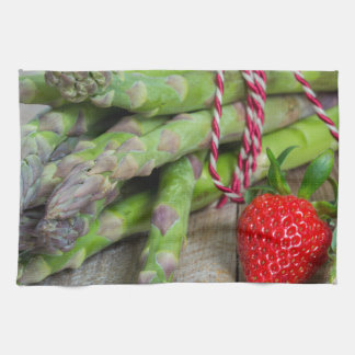 Green asparagus with strawberries on wooden kitchen towel