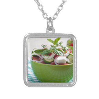 Green bowl with vegetable salad on tablecloth silver plated necklace