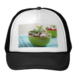Green bowl with vegetable salad on tablecloth trucker hat
