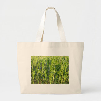 Green corn plants are growing in summer large tote bag