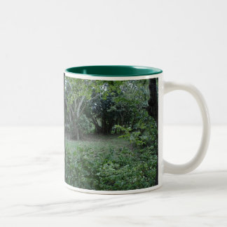 Green foliage frames an isolated grassy knoll Two-Tone coffee mug