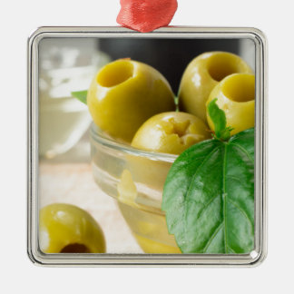 Green marinated olives pitted adorned with green Silver-Colored square ornament