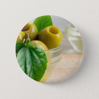 Green marinated olives pitted in a glass cup 2 inch round button