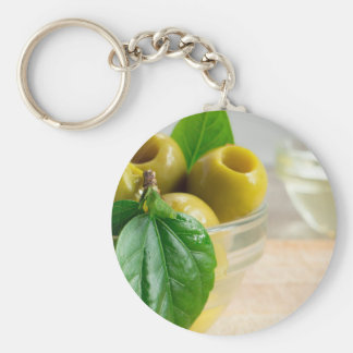 Green marinated olives pitted in a glass cup basic round button keychain