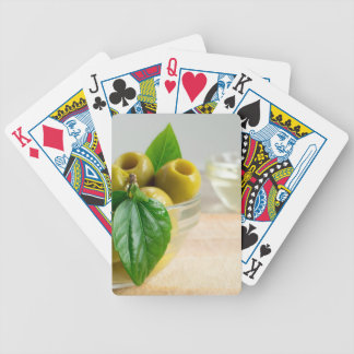 Green marinated olives pitted in a glass cup bicycle playing cards