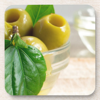 Green marinated olives pitted in a glass cup coaster