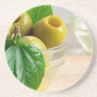 Green marinated olives pitted in a glass cup drink coaster
