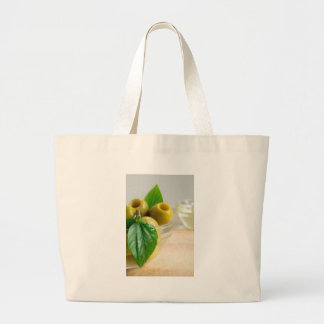 Green marinated olives pitted in a glass cup large tote bag