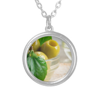 Green marinated olives pitted in a glass cup silver plated necklace