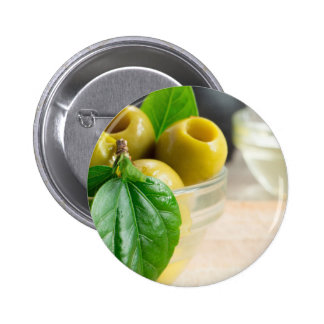 Green pickled pitted olives closeup 2 inch round button