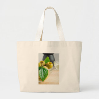 Green pickled pitted olives closeup large tote bag