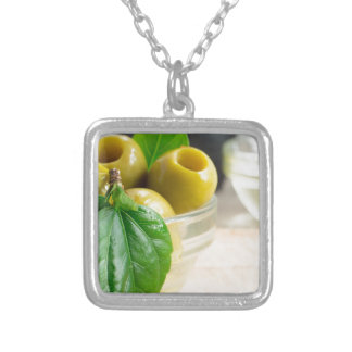 Green pickled pitted olives closeup silver plated necklace