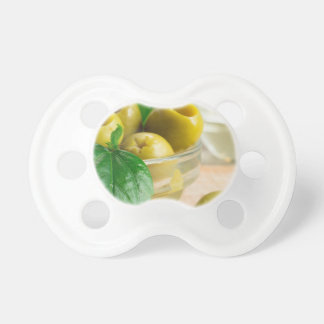 Green pickled pitted olives in a glass bowl pacifier