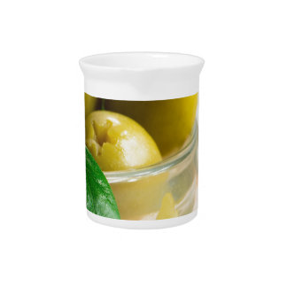Green pickled pitted olives in a glass bowl pitcher
