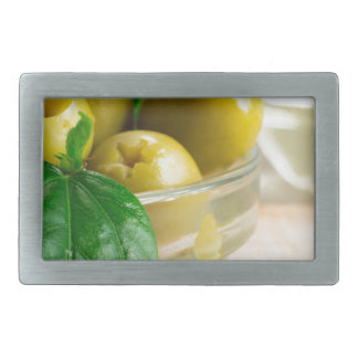 Green pickled pitted olives in a glass bowl rectangular belt buckles