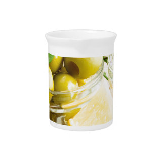 Green pitted olives decorated with herbs pitcher