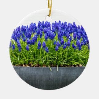 Grey metal flower box with blue grape hyacinths round ceramic ornament