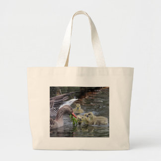 Greylag geese feeding goslings with plants on a la large tote bag