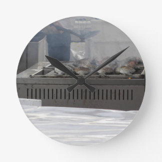 Grilling fish outdoors round clock