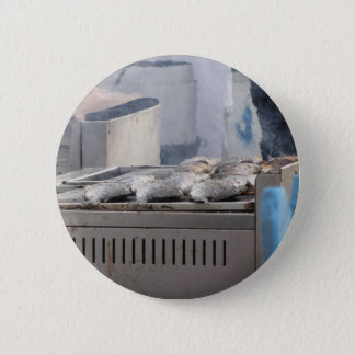 Grilling fish outdoors with smoke emerging 2 inch round button